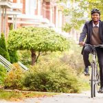 Single black male in his 30s cycling on urban sidewalk in Autumn