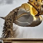 Construction industry excavator bucket loading gravel closeup
